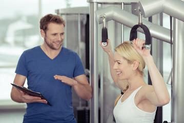 trainer im fitness-studio erklärt eine übung