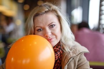 Depressed woman with orange balloon in restaurant