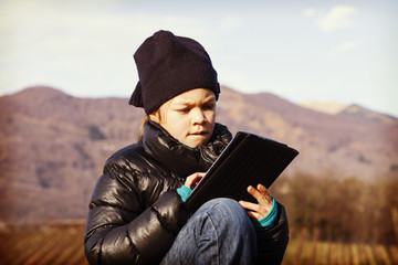 child looking her tablet during outdoor excursion