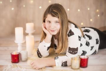 Junges Mädchen liegt zwischen Kerzen