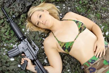 Soldat mit Gewehr trägt Bikini mit Tarnflecken