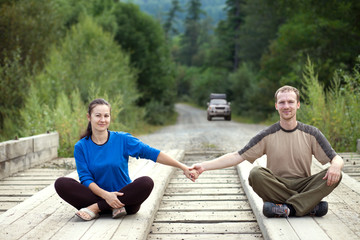 Tourist couple sitting on a wooden bridge and holding hands