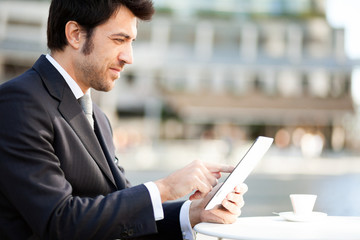 Businessman reading his digital tablet