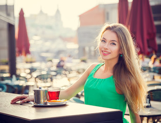 Young Woman Drinking Tea in a Cafe Outdoors.