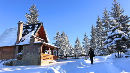 Woman walks past mountain houses on winter vacation