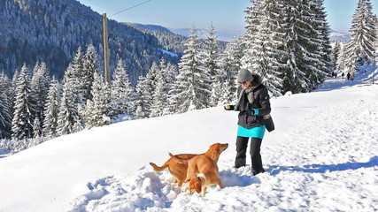 Happy woman plays with dogs in snow on mountain