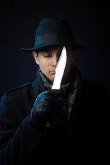 Man with a knife, studio shot, dark background