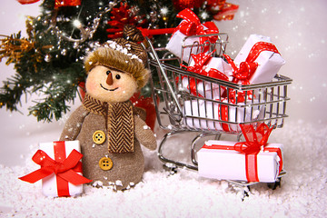 Smiling snowman and shopping cart with gifts