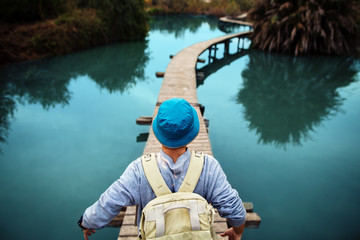 tourist man walking across wooden bridge over glossy blue lake