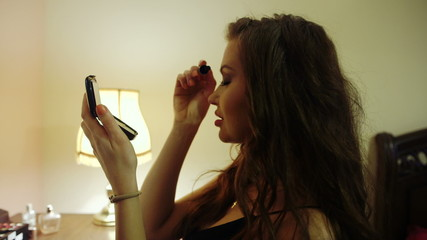Young beautiful woman applying mascara in her bedroom.