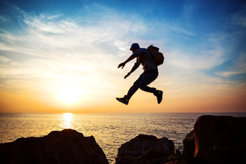 young brave man jumping over rocks near sea in sunset