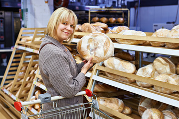 Young woman with bread in supermarket