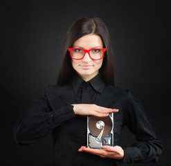 Girl in red-framed glasses showing a hard disk drive