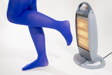 Feet in blue tights being warmed by an electric fire