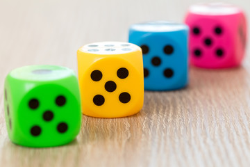 Four colorful dice on the wooden surface