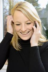 Frau mit Freude beim Telefonieren