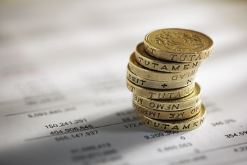 Stack of pound coins on financial figures