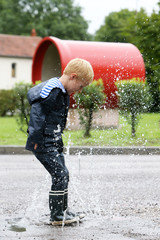 Little boy playing in a puddle