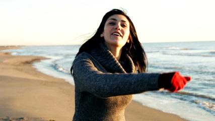 Happy woman dancing on the beach for boyfriend smilin