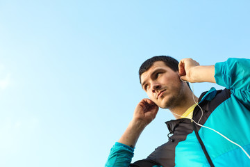 young sportsman put in earphones with music