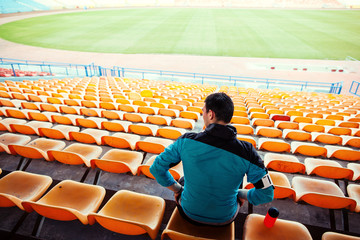 sportsman with a bottle of water sitting on chairs in stadium