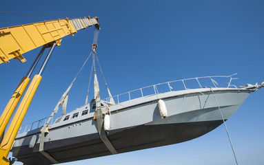 Boat being lifted by heavy crane machinery