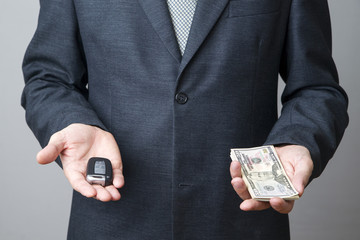 Businessman using car key and money