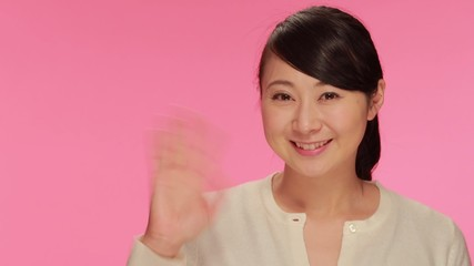 Young Asian woman waving hand smile face