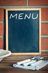 menu blackboard before brick wall