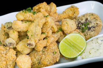 A basket of crispy chicken fingers with platter of vegetables an