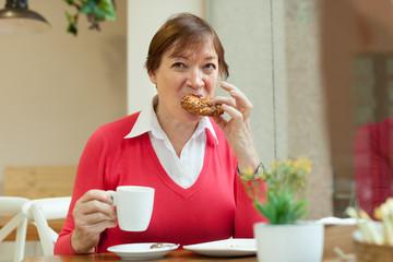 senior lady having  breakfast in   cafe.