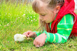 Child is lying in the grass with a small chicken