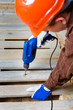 Worker drilling a plank