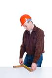 Portrait of an engineer in helmet making measurements