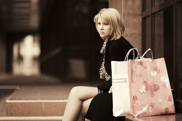 Sad young woman with shopping bags at the mall window