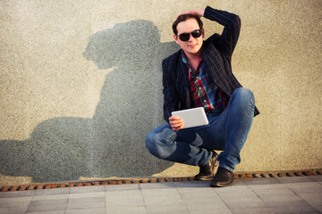 Young fashion man with a tablet computer sitting at the wall