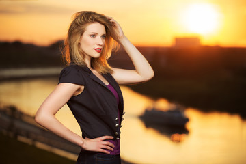 Happy young fashion woman at sunset