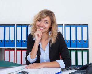 Lachende Frau mit blonden Locken im Büro