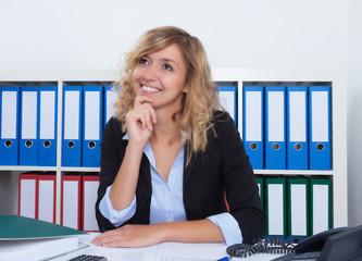 Frau mit blonden Locken träumt im Büro von der Zukunft