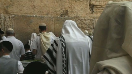 religious Jews in traditional white praying near Western Wall
