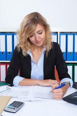Frau mit blonden Locken macht Notizen im Büro