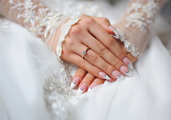 hands of a bride with a ring and a wedding manicure