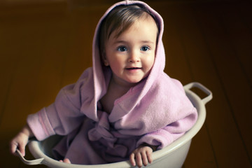 smiling baby in a bathrobe sits in a basin