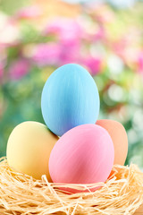 Painted Easter Eggs in nest on floral background