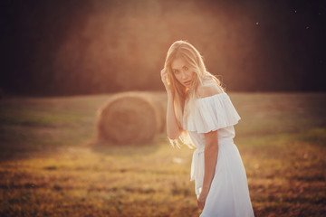 A pretty blonde girl posing in a field on summer