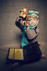 Little boy aviator dreaming and playing with wooden handmade toy