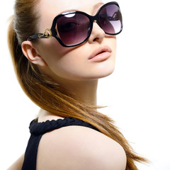 Fashion portrait of young pretty woman wearing sunglasses over w