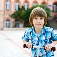 Cute boy riding two scooter