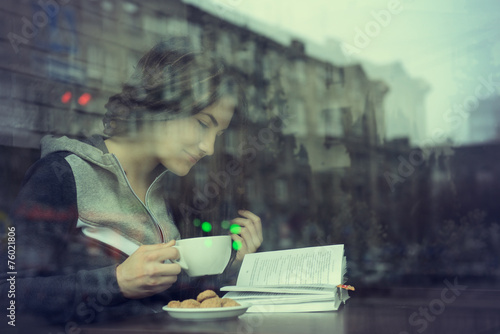 Young woman drinking coffee and reading book sitting indoor in u