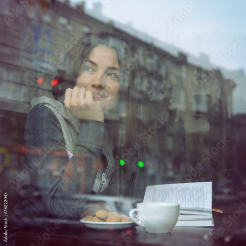 Young woman drinking coffee and reading book sitting indoor in u - 76022045